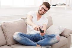 Hombre joven feliz en casa que juega a los videojuegos Foto de archivo libre de regalías