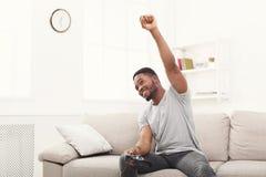 Hombre joven feliz en casa que juega los videojuegos y ganar Foto de archivo