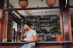 Hombre joven feliz en el café con un libro y un café de consumición Fotos de archivo