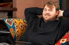 Hombre joven feliz en el sofá Imagenes de archivo