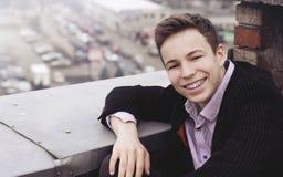 Hombre joven feliz en el tejado de una casa alta Imágenes de archivo libres de regalías