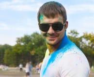 Hombre joven feliz en festival del color del holi Imagen de archivo
