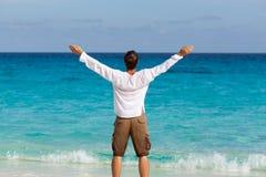 Hombre joven feliz en la playa imagen de archivo