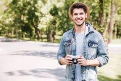 Hombre joven feliz en sombrero con la cámara vieja de la foto del vintage Fotografía de archivo