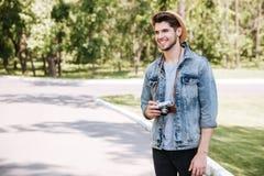 Hombre joven feliz en sombrero con la cámara vieja de la foto del vintage Foto de archivo