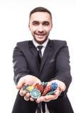 Hombre joven feliz en traje que soporta las fichas de póker del triunfo en el juego Fotografía de archivo libre de regalías