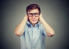 Hombre joven feliz hermoso que cubre sus oídos No oiga ningún concepto malvado Foto de archivo