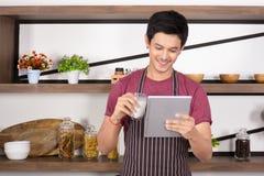 Hombre joven feliz llevar el delantal marrón que sostiene un vidrio de leche mientras que usa la tableta fotografía de archivo