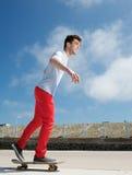 Hombre joven feliz que anda en monopatín al aire libre con el fondo del cielo azul Imagen de archivo