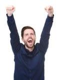 Hombre joven feliz que celebra con los brazos aumentados Imagenes de archivo
