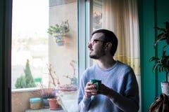 Hombre joven feliz que come una taza de café fotos de archivo