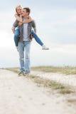 Hombre joven feliz que da a cuestas paseo a la mujer en rastro en el campo Fotografía de archivo