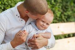Hombre joven feliz que detiene a un bebé sonriente Foto de archivo libre de regalías