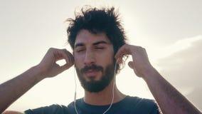 Hombre joven feliz que disfruta de la música en los auriculares metrajes