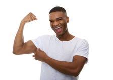 Hombre joven feliz que dobla el músculo del bíceps Fotografía de archivo