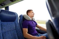 Hombre joven feliz que duerme en autobús del viaje con la almohada Fotos de archivo libres de regalías