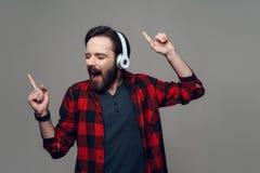 Hombre joven feliz que escucha la música con los auriculares fotografía de archivo