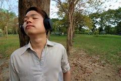 Hombre joven feliz que escucha la música con los auriculares y que inclina un árbol en el parque al aire libre público Imagenes de archivo
