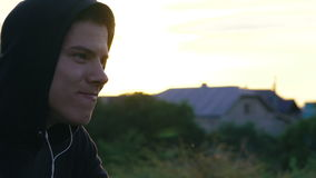 Hombre joven feliz que escucha la música en auriculares en la naturaleza metrajes