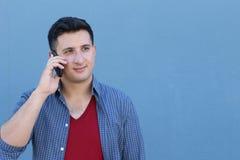 Hombre joven feliz que habla en el teléfono celular aislado en fondo azul Imagen de archivo libre de regalías