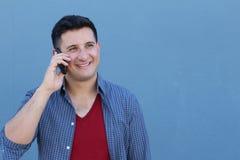 Hombre joven feliz que habla en el teléfono celular aislado en fondo azul Imagen de archivo