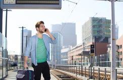 Hombre joven feliz que habla en el teléfono móvil en la plataforma de la estación de tren Fotografía de archivo
