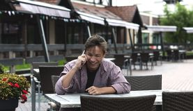 Hombre joven feliz que habla en el teléfono que se sienta en la tabla Foto de archivo libre de regalías