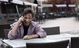 Hombre joven feliz que habla en el teléfono que se sienta en la tabla Imagen de archivo