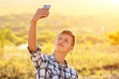 Hombre joven feliz que hace un selfie en el teléfono y que sonríe, fondo natural en la luz del sol fotografía de archivo