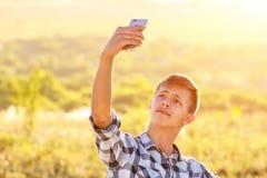 Hombre joven feliz que hace un selfie en el teléfono y que sonríe, fondo natural en la luz del sol foto de archivo