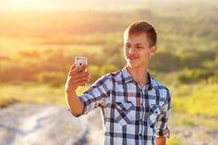 Hombre joven feliz que hace un selfie en el teléfono y que sonríe, fondo natural en la luz del sol fotografía de archivo libre de regalías