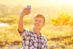 Hombre joven feliz que hace un selfie en el teléfono y que sonríe, fondo natural en la luz del sol Imagenes de archivo