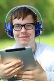 Hombre joven feliz que lleva a cabo un ipad Fotos de archivo libres de regalías