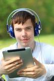 Hombre joven feliz que lleva a cabo un ipad Imagenes de archivo
