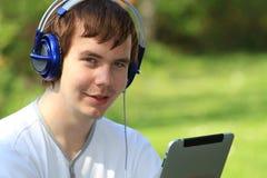 Hombre joven feliz que lleva a cabo un ipad Imagen de archivo