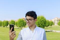 Hombre joven feliz que mira en teléfono con gran sonrisa Imagenes de archivo