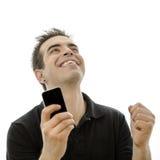 Hombre joven feliz que mira su smartphone Fotos de archivo