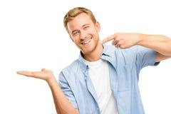 Hombre joven feliz que muestra el copyspace vacío en el fondo blanco Foto de archivo libre de regalías