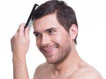 Hombre joven feliz que peina el pelo. Imagenes de archivo
