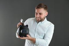 Hombre joven feliz que pone el dinero en la hucha en fondo fotografía de archivo