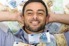 Hombre joven feliz que pone en billetes de banco imagenes de archivo