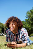 Hombre joven feliz que ríe con el teléfono móvil y los auriculares en parque Fotografía de archivo libre de regalías