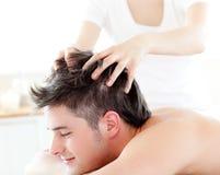 Hombre joven feliz que recibe un masaje principal Fotos de archivo