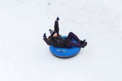 Hombre joven feliz que resbala abajo en el tubo de la nieve Imágenes de archivo libres de regalías