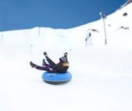 Hombre joven feliz que resbala abajo en el tubo de la nieve Fotos de archivo