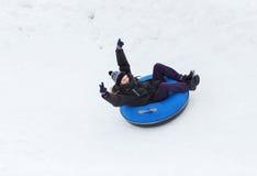 Hombre joven feliz que resbala abajo en el tubo de la nieve Imagen de archivo libre de regalías