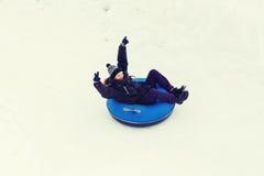 Hombre joven feliz que resbala abajo en el tubo de la nieve Foto de archivo
