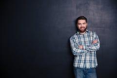 Hombre joven feliz que se coloca con los brazos doblados Fotografía de archivo