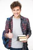Hombre joven feliz que se coloca con los libros Foto de archivo libre de regalías