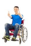 Hombre joven feliz que se incorpora en una silla de ruedas y un pulgar Fotos de archivo libres de regalías